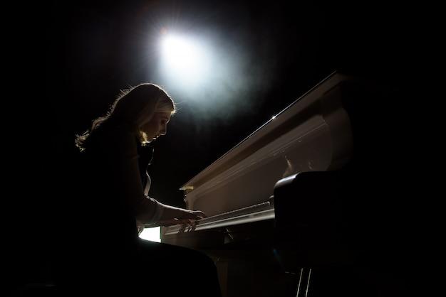 Cerrar vista de una niña toca el piano en la sala de conciertos en la escena