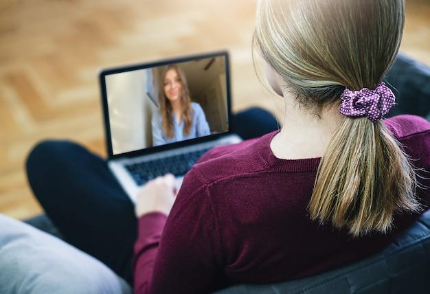Cerrar vista posterior de mujer joven tiene reunión en línea de cámara web con colega