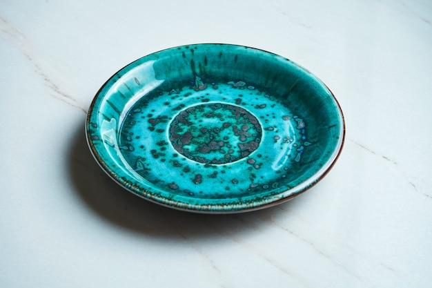 Cerrar vista sobre placa de cerámica azul vacía hecha a mano sobre una superficie de mármol gris. copiar espacio para texto. utensilios de cocina con estilo