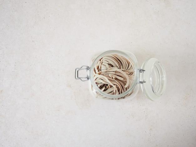 Cerrar la vista superior del frasco abierto lleno de pasta de tallarines de trigo integral