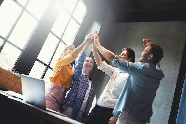 Cerrar vista superior de jóvenes empresarios juntando sus manos pila de manos trabajo en equipo