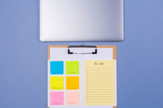 Cerrar vista superior de la lista de tareas en blanco para la semana y el portátil sobre fondo morado claro, plano. copia espacio espacio libre. calendario. calendario.