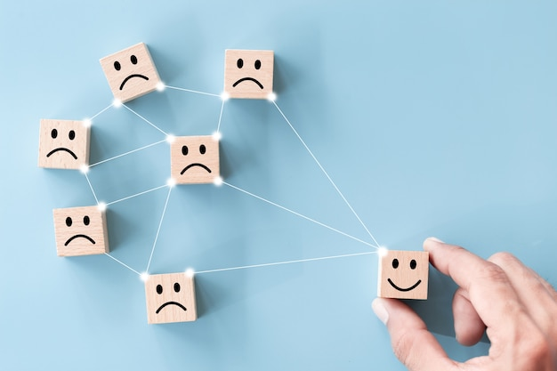 Cerrar vista superior mano del cliente elegir cara sonriente en cubo de madera