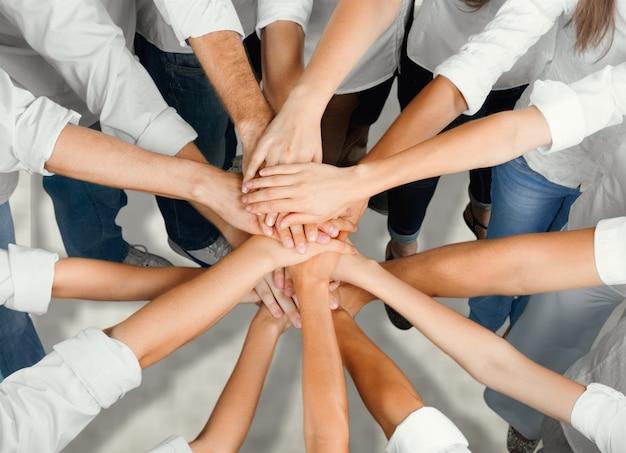 Cerrar vista superior de personas juntando sus manos, concepto de trabajo en equipo
