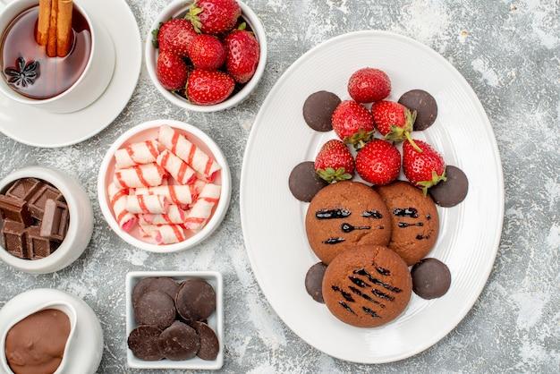 Cerrar vista superior tazones de galletas, fresas y chocolates con caramelos de cacao, fresas, chocolates y té con canela en la mesa gris-blanca