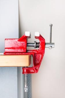 Cerrar vista de un tornillo de mesa de metal sujeto en una mesa.