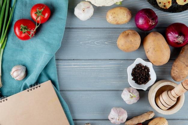 Cerrar vista de verduras como tomate ajo cebolla con pimienta negra y trituradora de ajo sobre fondo de madera con espacio de copia