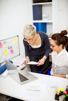 Cerrar vista vertical de dos mujeres productivas profesionales enfocadas que trabajan juntas una junto a otra en una computadora portátil en la oficina.