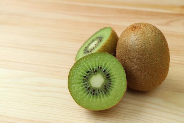 Cerró secciones transversales de kiwi fresco y maduro con una fruta entera aislada en una mesa de madera