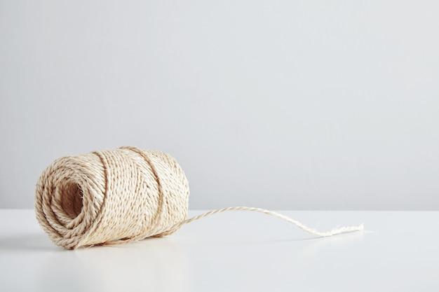 Cerrojo de cuerda artesanal aislado en el lateral de la mesa blanca