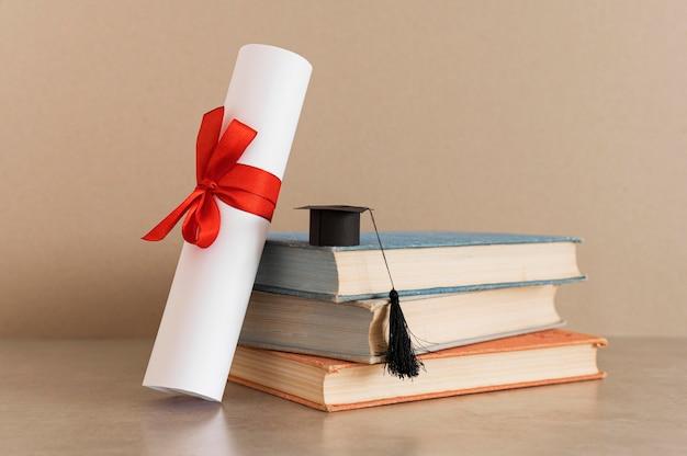 Certificado de diploma de educación y pequeño sombrero de graduación.