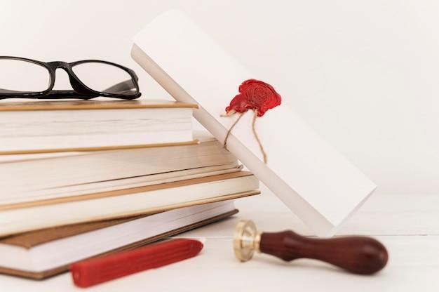 Certificado de diploma de graduación y pila de libros.