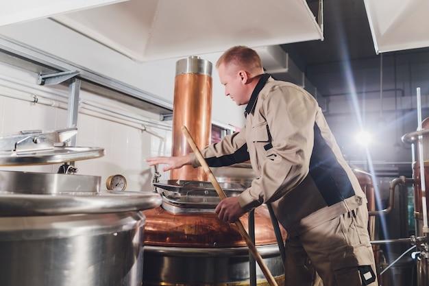 Cervecero en cervecería vertiendo la malta al tanque.