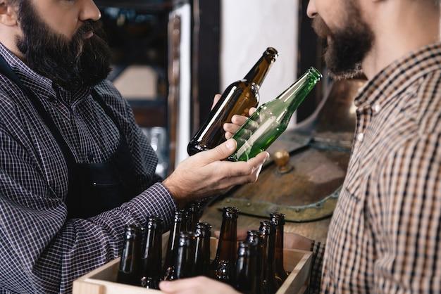 Cervecero escogiendo botella de cerveza marrón y cristal verde.