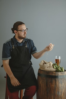 Cervecero masculino joven confiado con cerveza artesanal en vidrio en barril de madera en gris