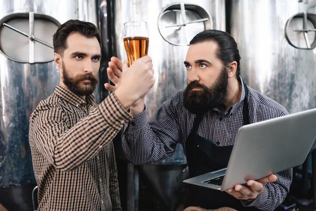 Cerveceros que monitorean la calidad de la cerveza con vidrio