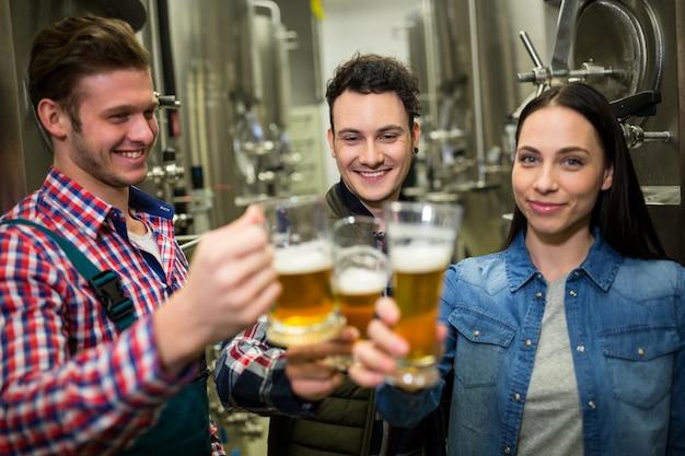 Cerveceros que tuestan cervezas en la fábrica de cerveza