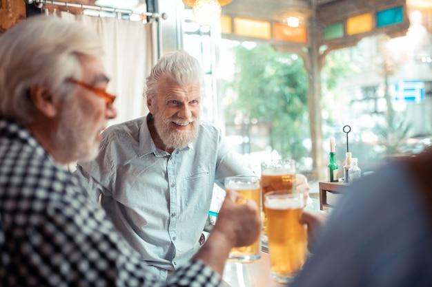 Cerveza con amigos. hombre canoso barbudo sonriendo mientras bebe cerveza con amigos