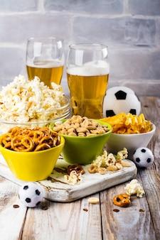 Cerveza y aperitivos en mesa de madera.