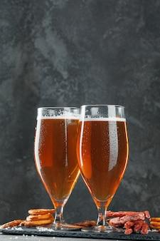 Cerveza y apetitosos aperitivos de cerveza. mesa con jarra de cerveza, tabla de madera con salchichas
