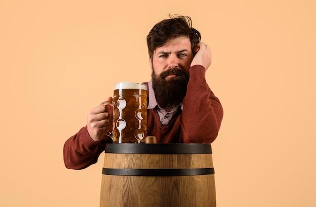 Cerveza artesanal en el restaurante oktoberfest hombre serio con barril de cerveza de madera y jarra de cerveza cervecera