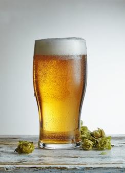 Cerveza. cerveza artesanal fría ligera en un vaso. alrededor de los lúpulos. pinta de cerveza cerrar