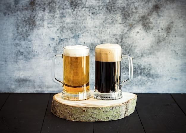 Cerveza clara y oscura en tazas sobre tabla de madera