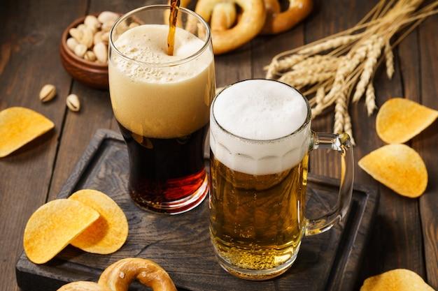 Cerveza clara y oscura con varios bocadillos: papas fritas, pretzels y nueces en una mesa de madera oscura.