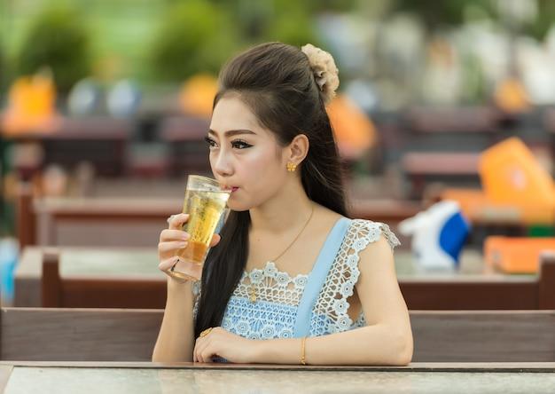 Cerveza de consumición de la mujer en el café. hermosa joven asiática