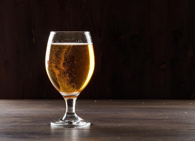 Cerveza en una copa de vidrio vista lateral sobre una mesa de madera