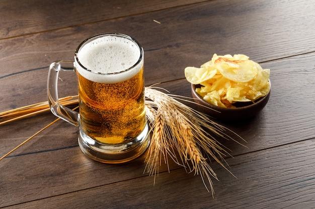 Cerveza con espigas, chips en un vaso en la mesa de madera, vista de ángulo alto.