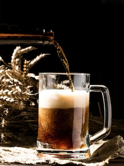 Cerveza espumosa vertida en la taza que se coloca en el fondo de madera vacío