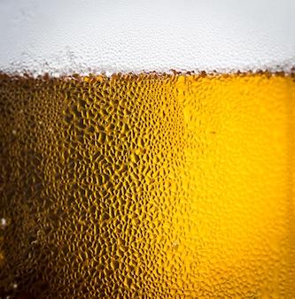 Cerveza de fondo y burbujas con gotas de condensación en el exterior del vaso