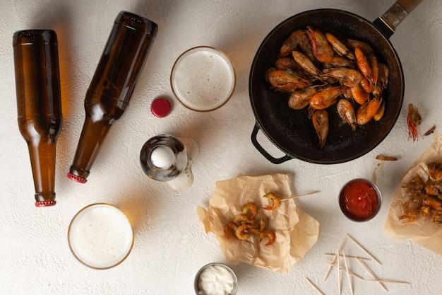 Cerveza fresca con camarones fritos en una mesa de luz, vista superior