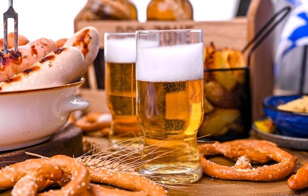 Cerveza fresca con espuma en madera. oktoberfest pretzels alemanes.