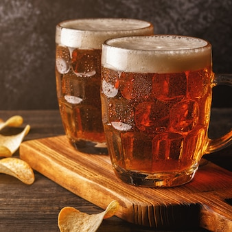 Cerveza fría en vaso con patatas fritas en una mesa oscura.