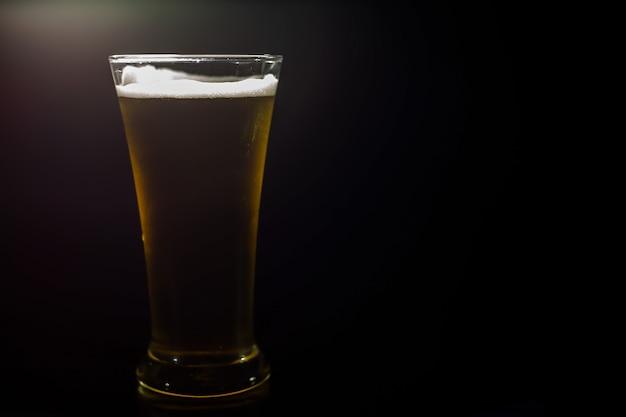 Cerveza fría en un vaso sobre un fondo oscuro
