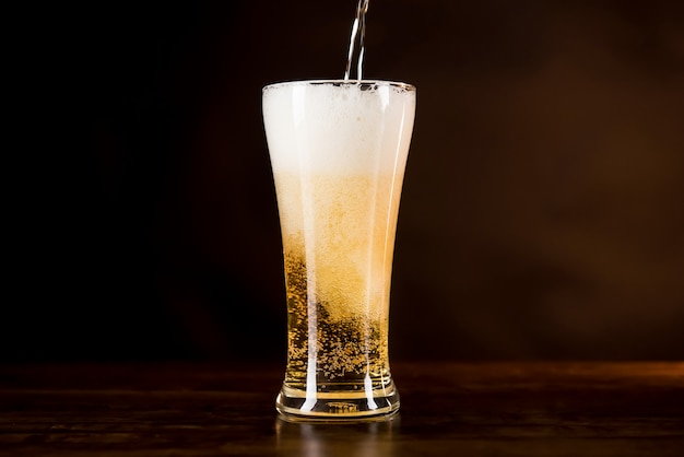 Cerveza fría se vierte en el vaso con espuma espumosa en la parte superior