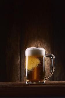 Cerveza en jarra sobre mesa de madera