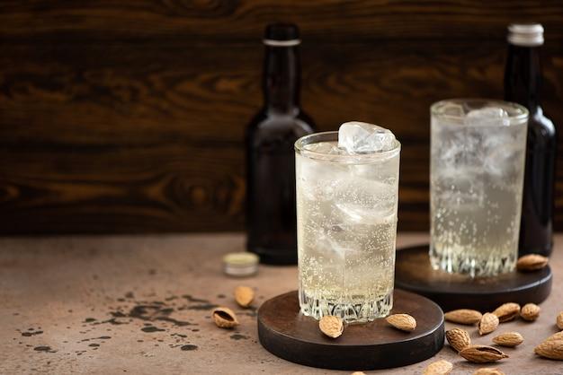 Cerveza de jengibre sin alcohol con hielo en vasos altos sobre una mesa de madera