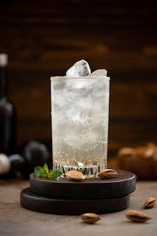 Cerveza de jengibre sin alcohol con hielo en vasos altos sobre una mesa de madera Foto Premium