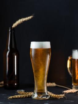 Cerveza ligera fría en un vaso sobre una mesa oscura