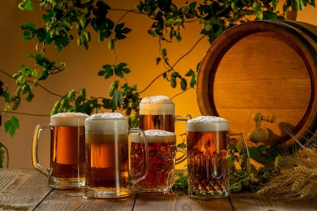 Cerveza ligera en vasos de cerveza cerca de un barril sobre un fondo