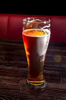 Cerveza light en un vaso sobre una mesa de madera