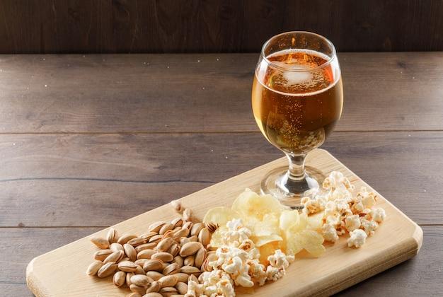Cerveza con merienda en un vaso de vidrio en la mesa de madera y tabla de cortar, vista de ángulo alto.