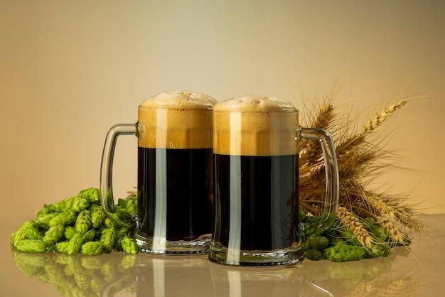 Cerveza negra en vasos con lúpulo y trigo.