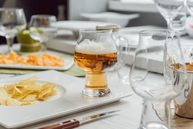 Cerveza y papas fritas en una gran mesa blanca