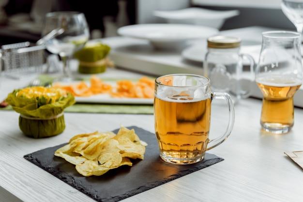 Cerveza y papas fritas en la gran mesa blanca