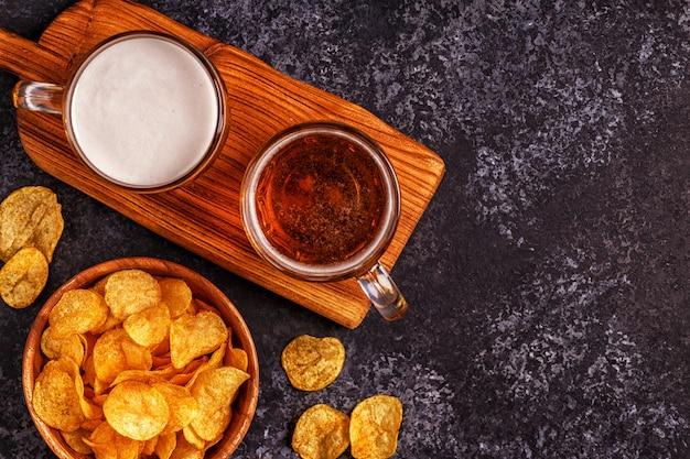 Cerveza y patatas fritas crujientes sobre la superficie de piedra