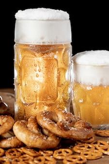 Cerveza de primer plano con espuma y bocadillos.